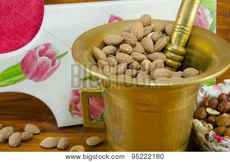 Hazelnuts In A Old Mortar With An Decoupage Decorated Tray In Background On A Table With Nuts And Al
