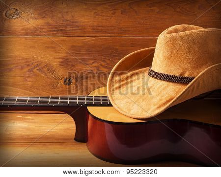 Guitar And Cowboy Hat On Wood Background