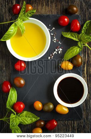 Fresh Tomatoes, Basil, Olive Oil And Balsamic Vinegar On Wooden Background With Black Board
