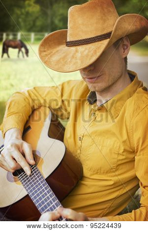 Handsome Man In Cowboy Hat Playing Guitar