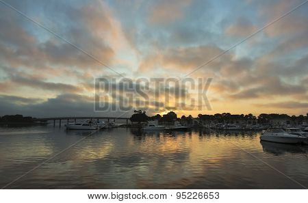 A Gorgeous Sunrise Over A Bridge And Marina