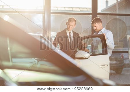 Businessman Watching Car In Showroom