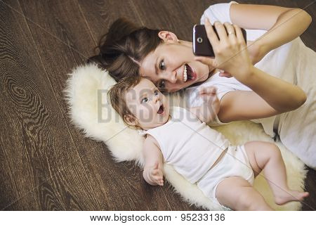 Woman With A Baby Doing A Selfie Lying On Floor