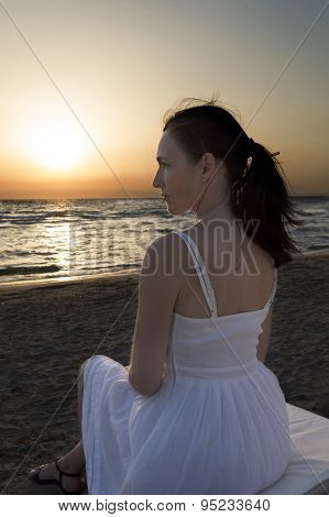 Woman Sitting On Sun Lounger And Looking At Sunset