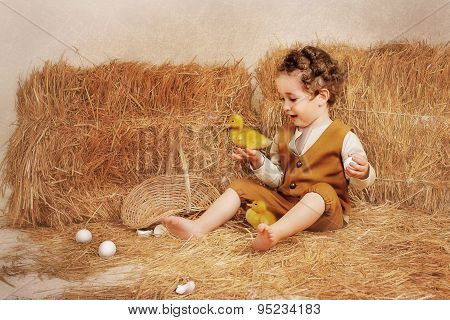 Beautiful Curly-haired Boy With Ducklings Near Hay