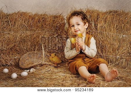 Beautiful Curly-haired Boy Sitting Next To A Hay Duckling In Hands