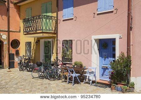 Exterior of the old residential building with bicycles parked at the entrances in Rimini, Italy.