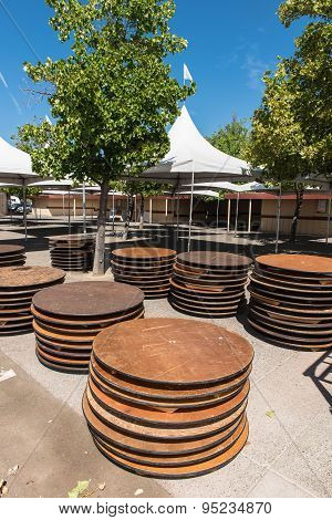Round Tables Stacked Outdoors By Tent