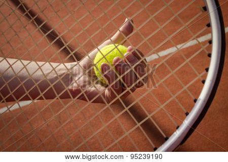 Hand Holding Tennis Ball Through Racket String