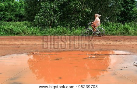 Young Woman Riding Bicycle In Tropical Summer Rain