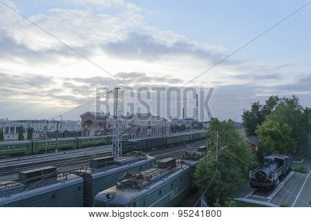 Railway Station With Trains (passenger And Freight) Under A Blue Evening Sky With Clouds