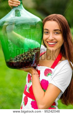 Woman holding big bottle with red berries in the garden