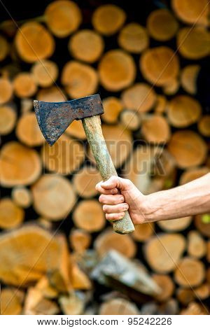 Holding an ax on firewood background