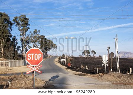 Burnt Farm Field With Railway Crossing In Foreground