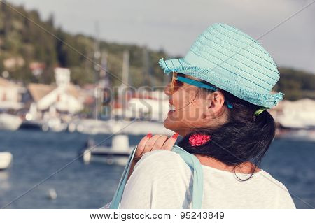 Woman with a hat looking at the sea during sunset