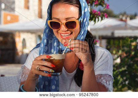 Happy young woman drinking iced coffee in restaurant