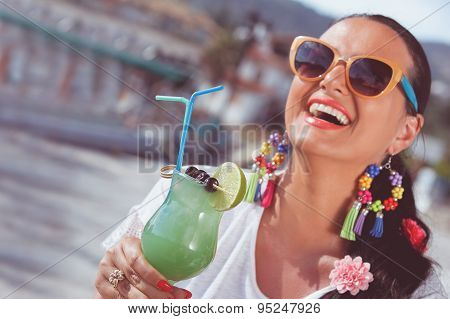 Happy young woman  holding a glass of cocktai