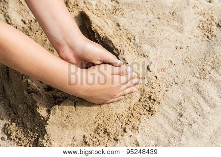 Child hand on a sand