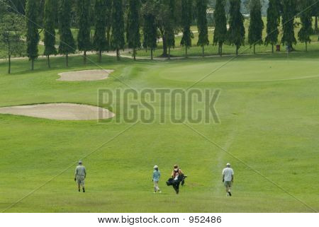 Golf Players Walking Towards The Green