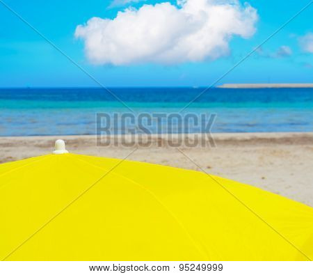 Yellow Parasol Under A Cloudy Sky In Alghero
