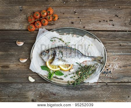 Roasted dorado or sea bream fish with vegetables, herbs and spices on silver tray over rustic wood b