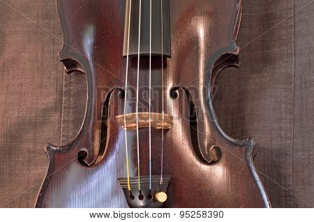 Antique Violin Closeup Against Gray Fabric Background