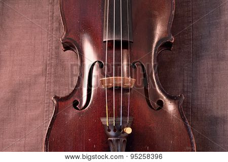 Antique Violin Against Gray Fabric Background
