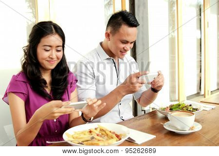 Young Couple Taking Photos Of Their Food