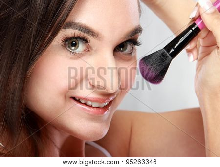 Beautiful Woman Smiling While Applying Blush On