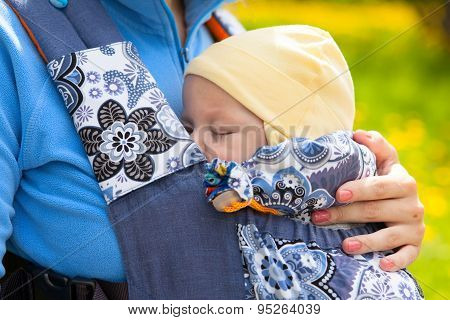 Newborn Baby And Mother Outdoors Walking With Sling.