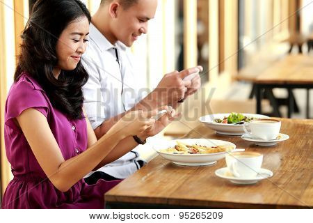 Funny Couple Taking Photos Of Their Food