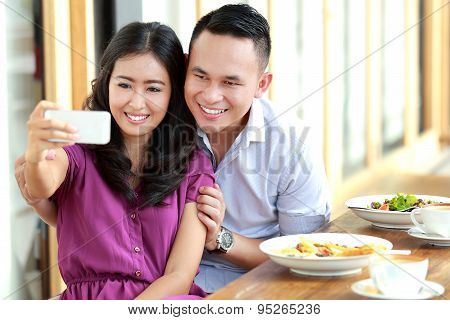 Young Couple Taking A Photo Of Them Using Mobilephone Camera
