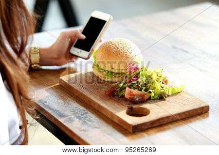 Woman Holding Mobilephone And Having A Burger For Lunch