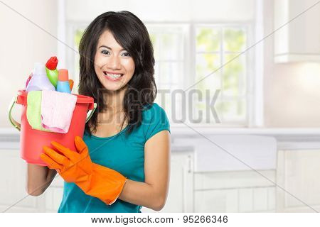 Beautiful Young Asian Woman Holding A Basket Full Of Cleaning Products In Right Hand