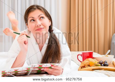 Young Woman With A Notebook And Breakfast In Bed