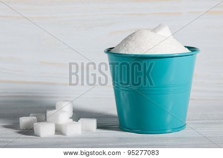 White cubes sugar and bucket of granulated sugar