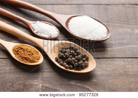 Collection Set Of Spices On Wooden Spoons. ( Black Pepper, Salt , Paprika, Sugar)