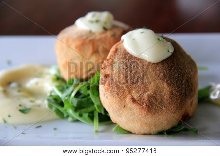 Two delicious crab cakes with lemon caper remoulade served over a bed of arugula
