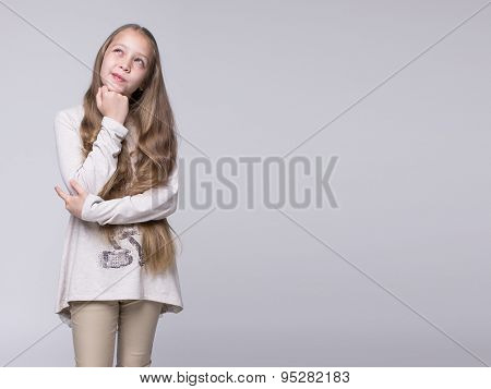 portrait of bewildered teenage girl standing on a gray background