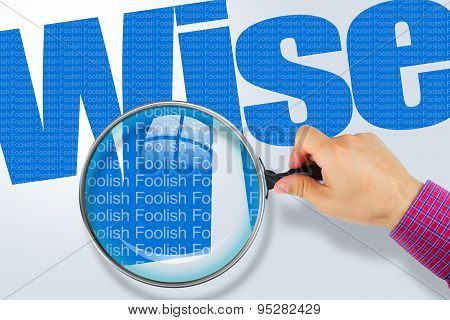 Wise - Foolish Opposite Message, Hand Holding Magnifying Glass