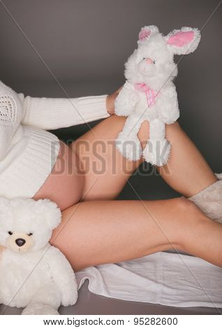 Toy bear cub against a stomach of the pregnant woman. The pregnant woman with a toy bear cub are wal