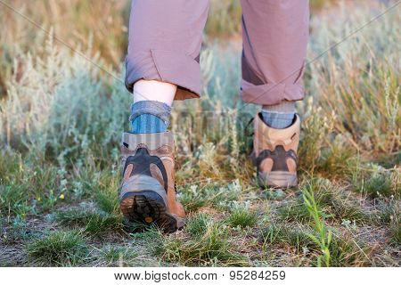 Feet of hiker walking on trail