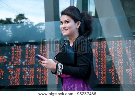 Business Woman Trade Stock On Mobile Near Exchange Board