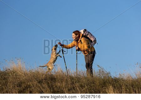Happy smiling woman hiking in mountains with dog Young