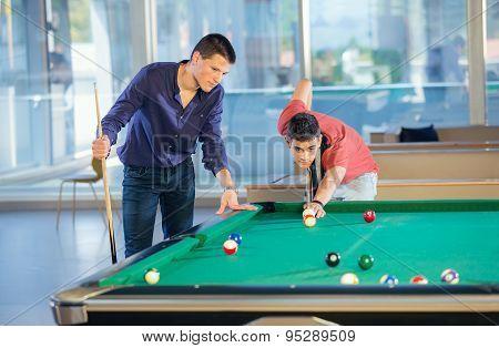Two guys in pool billiard club playing pool billiard