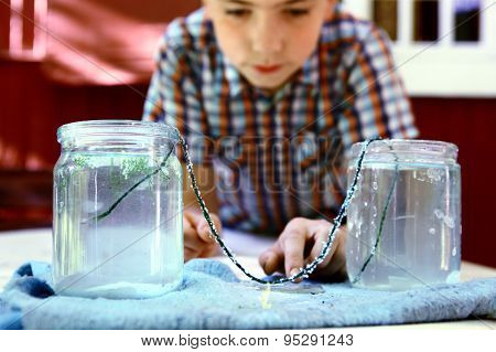 preteen handsome boy make an outdoor chemical test with carbonated water and cristal growth