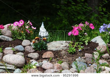 Flowerbed In A Garden Of Flowers, Embellished With Stones And Dwarf