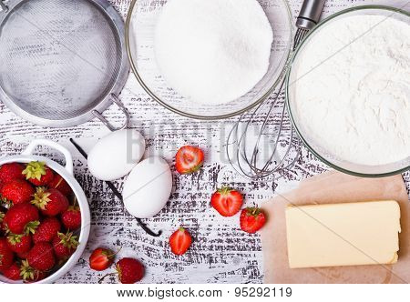 Ingredients For Making Strawberry Cake On White Wooden Background