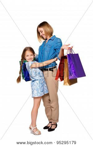 Happy  mother and daughter with shopping bags standing at studio