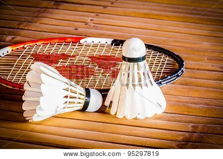Shuttlecock With Racket On Bamboo Table